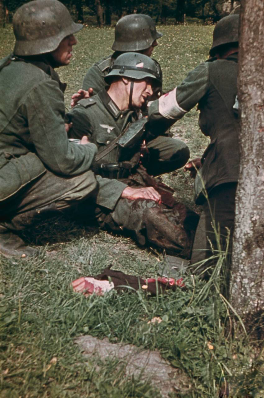 German_soldiers_comforting_wounded_comrade_who_has_just_had_his_arm_foreground_blown_off_in_the_bloody_East_Front_fighting_1942.jpg